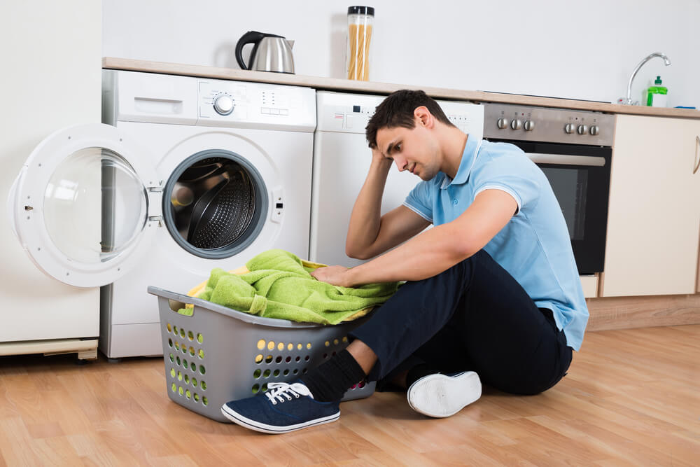 Man sitting next to broken washing machine