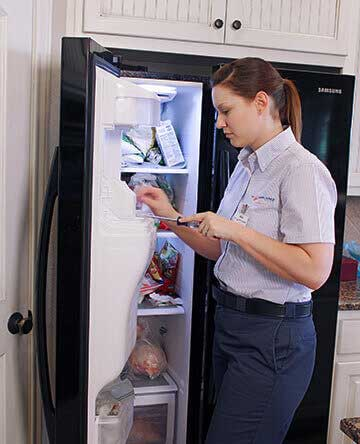 Mr. Appliance technician examining a refrigerator