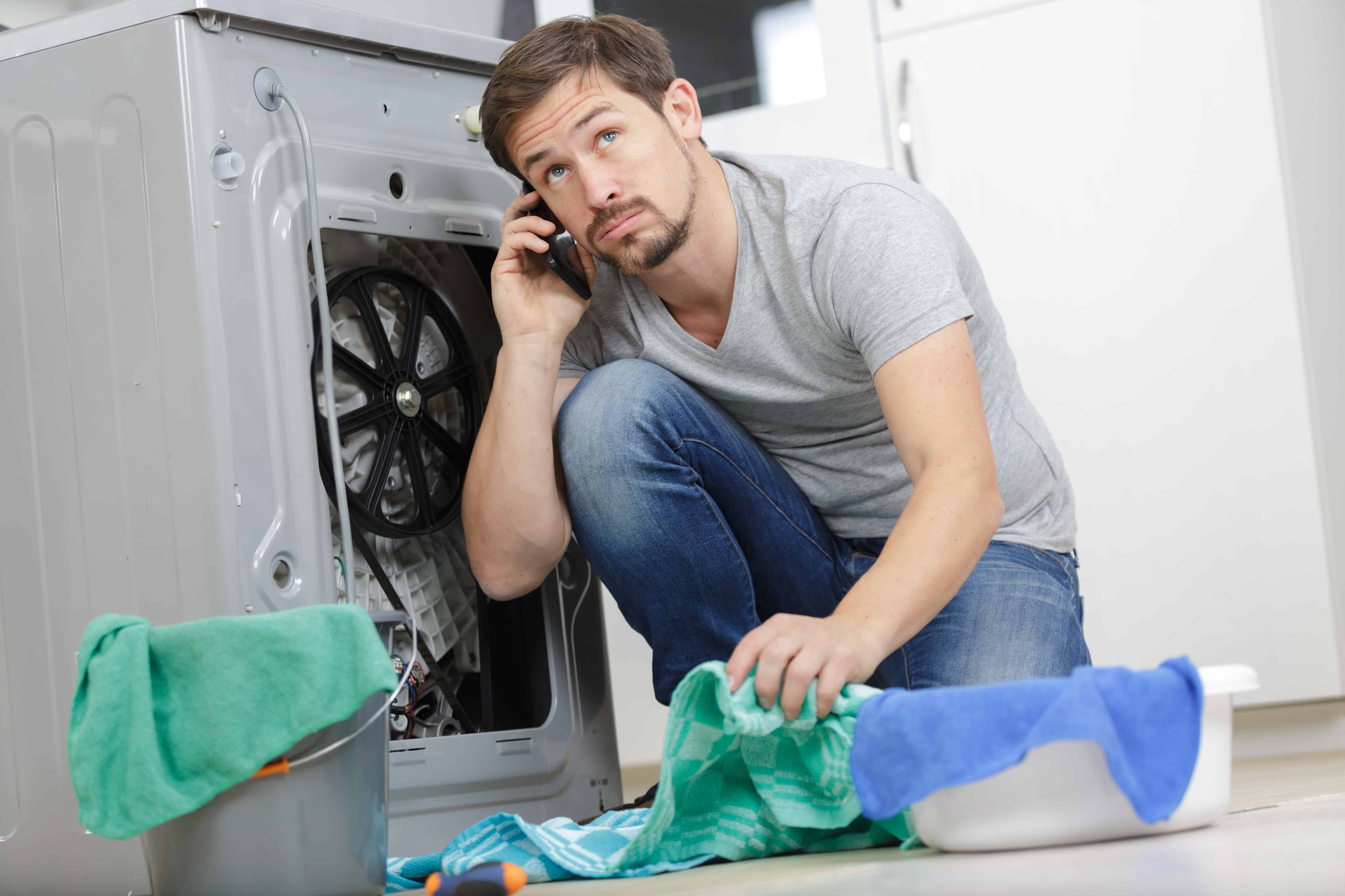Man Cleaning Up After a Broken Washer
